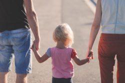 dziecko trzyma się za ręce z rodzicami